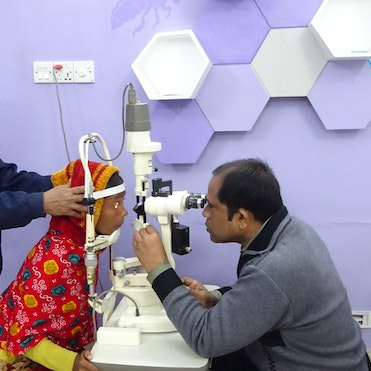 Bangladeshi paediatric patient Tania undergoes an eye examination while someone holds her head still