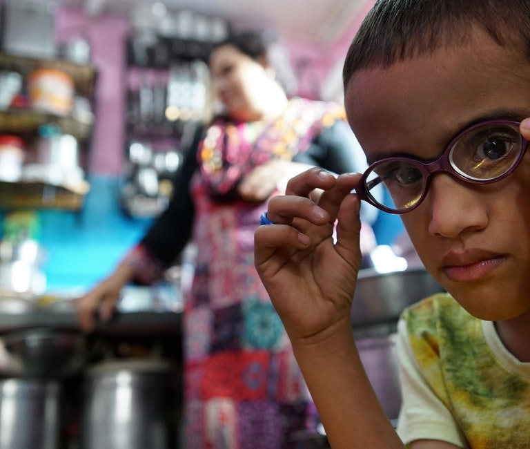 Paediatric patient Ismail from Bangladesh looking through his glasses