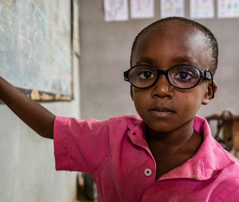 Paediatric patient Saliou writes with chalk on the board of his schoolroom, wearing glasses
