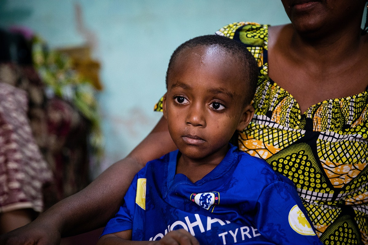 Paediatric patient Saliou, wearing a blue football shirt, sits on his mother's lap