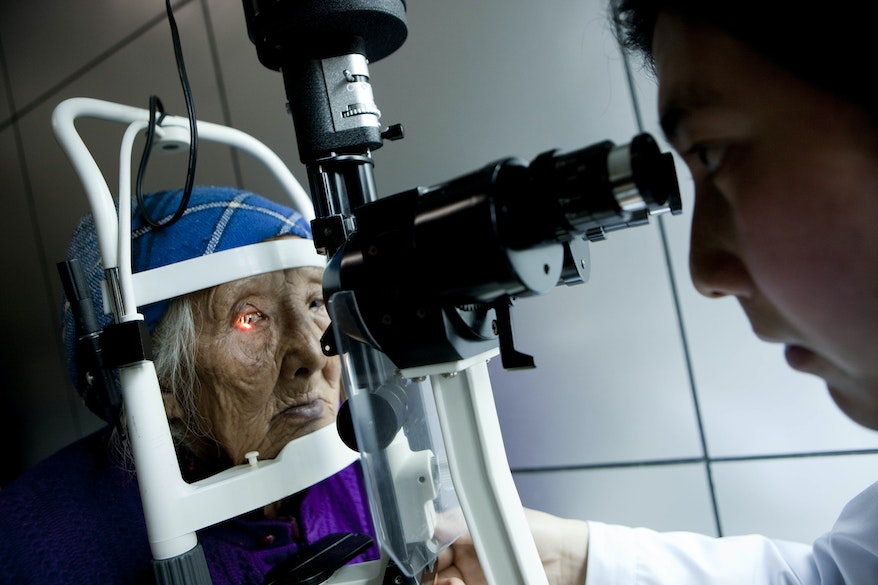 An optometrist examines an elderly Chinese woman