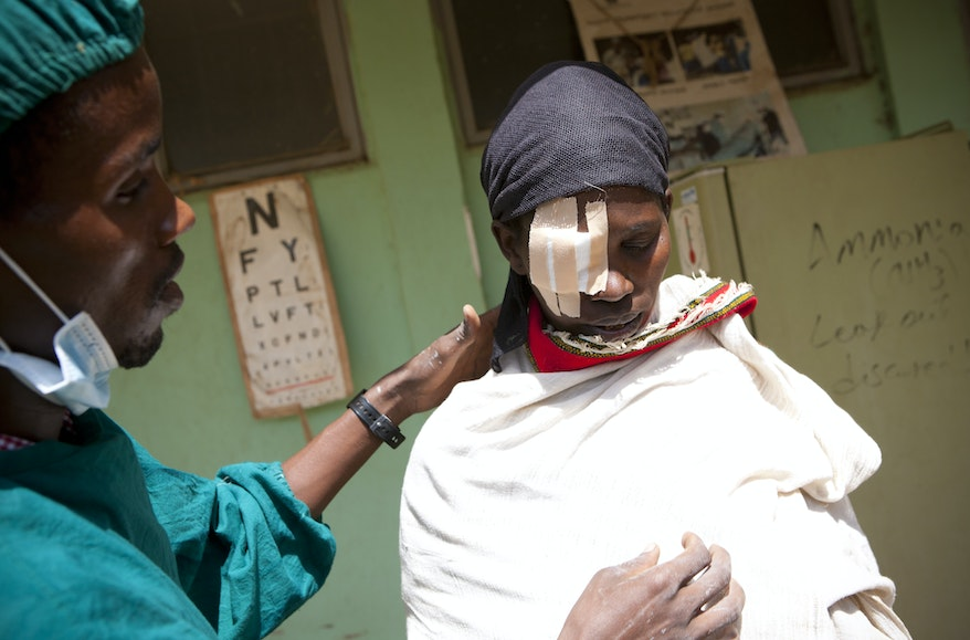 Ethiopiant trachoma patient Aylito after surgery. She looks down, an eye patch covering her right eye, her chest covered in a blanket
