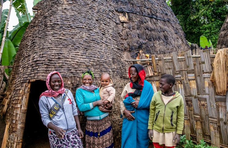 An Ethiopian family stands outside their home, holding a young child
