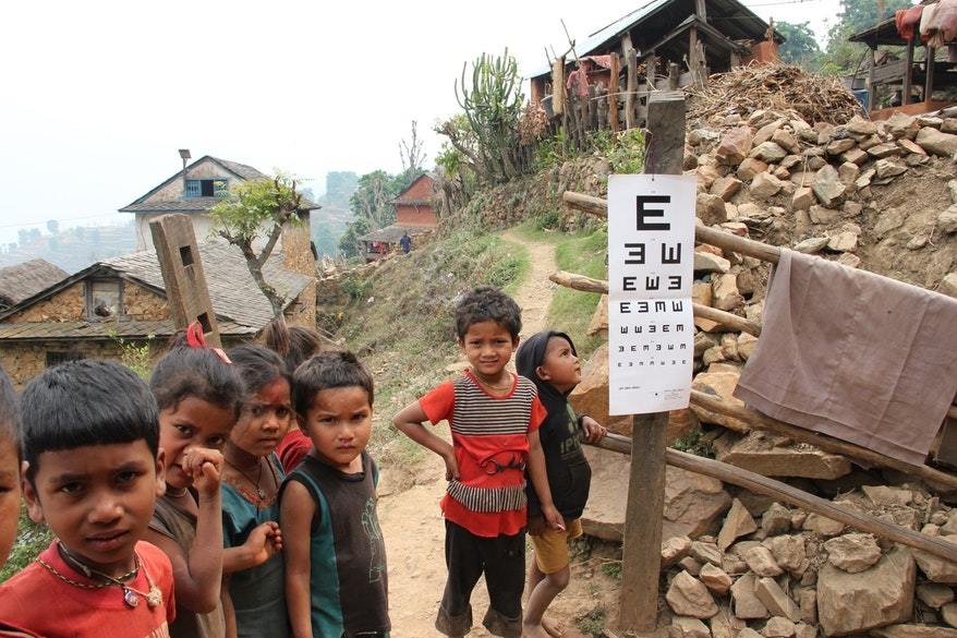 Small children in a rural Indian village stand by an eye test stuck onto a post as part of the India Childhood Blindness Initiative (IBCI)