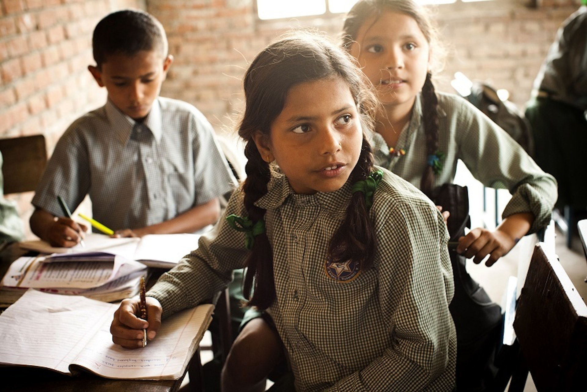 Nepalese school children sit and learn at Laxman Ganj village school. The girl in the foreground has long plaited hair and is writing, as are her peers