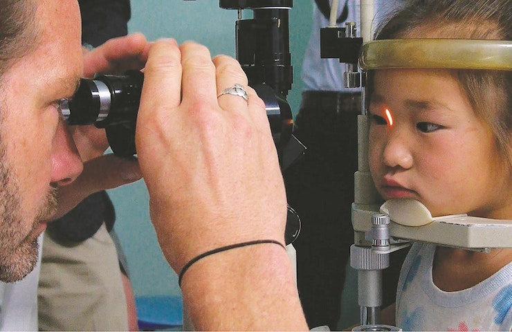 Paediatric patient Enkhzul getting an eye examination, a light shone into her eyes
