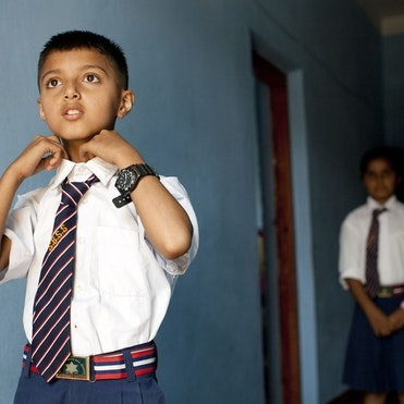 Young boy doing up his school tie.