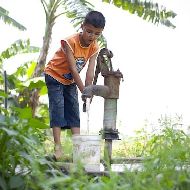 Child getting water from a pump.