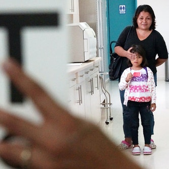 A small child walks along a hospital corridor, her mother covering one eye with her hand
