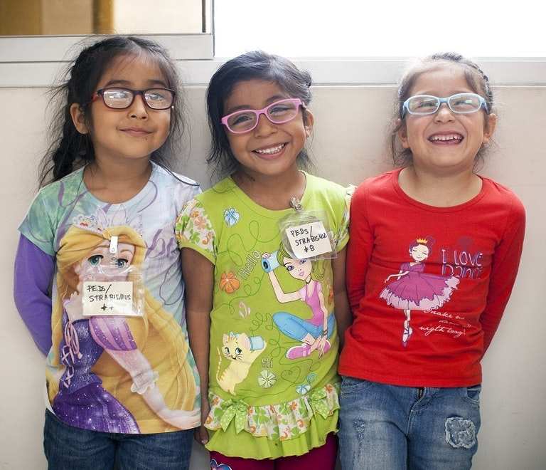 Three children with glasses, smiling at the camera
