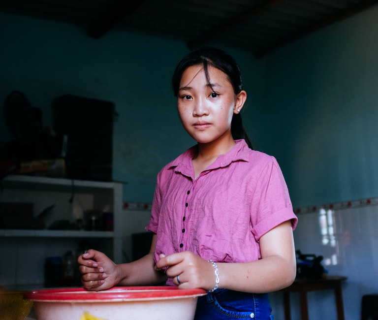 Trinh from Vietnam looks into the camera. She is wearing a pink top. She had surgery on the Orbis Flying Eye Hospital to correct strabismus