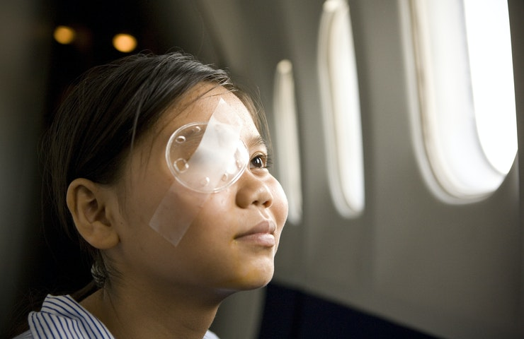 A young Vietnamese patient wearing an eye dressing looks out of the Flying Eye Hospital window