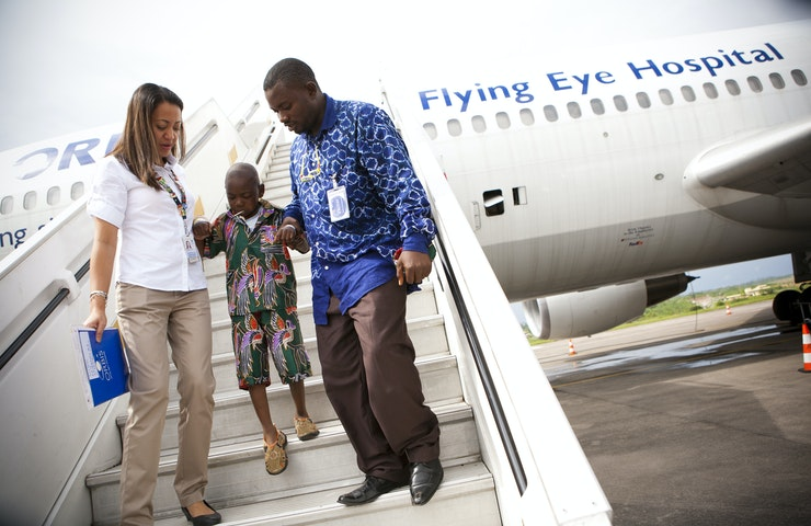 A patient walks down the stairs of the Flying Eye Hospital, his hand being held