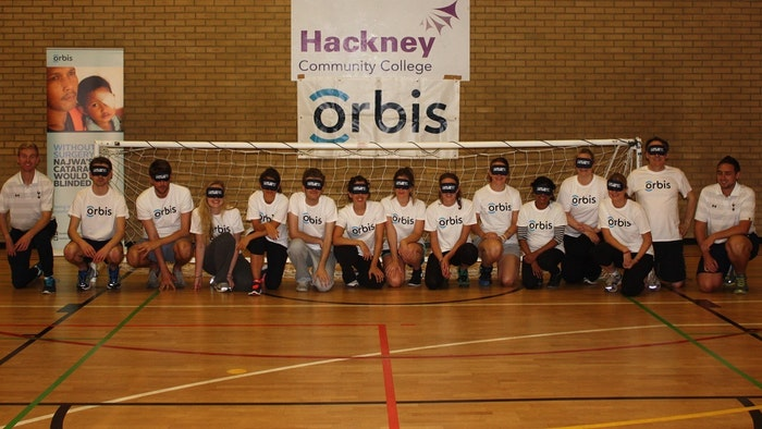 Blindfolded footballers and their coach kneel by a goal with the Orbis logo displayed