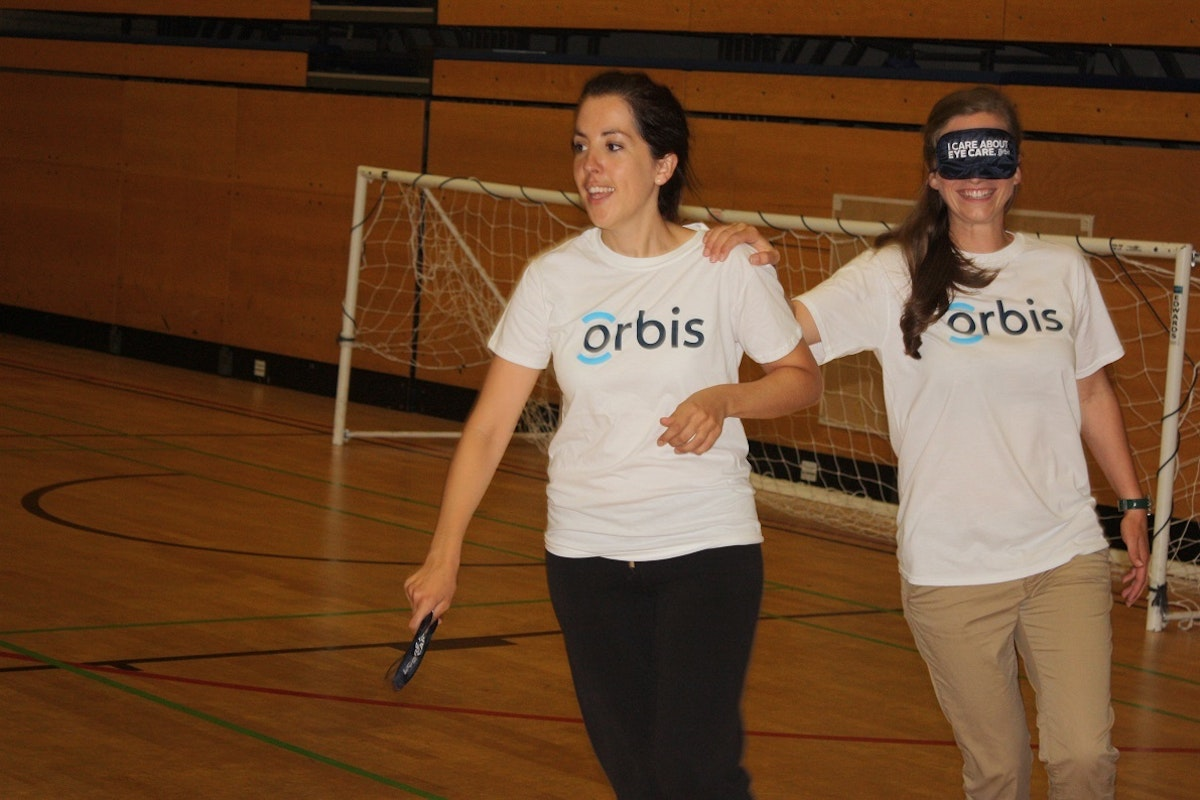 Two women play blind football - one is blindfolded and has her hand on the other's shoulder
