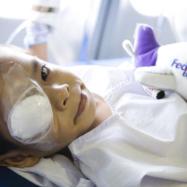 Young patient Iloilo from the Philippines, wearing an eye patch, looks into camera, holding a toy FedEx plane to his chest