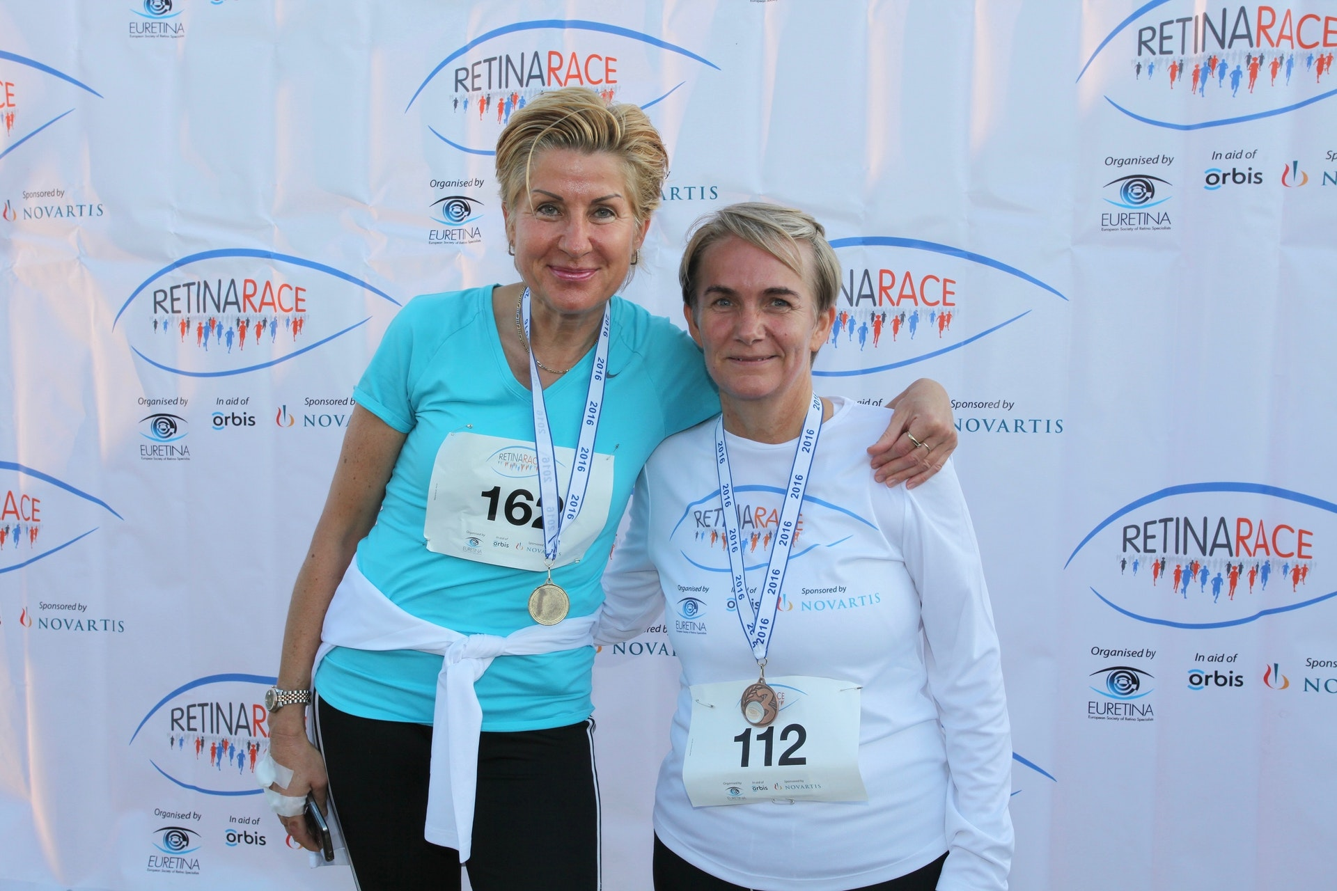 Two female participants in the Retina Race 2016 look into the camera, their arms around each other, medals hanging down from their necks