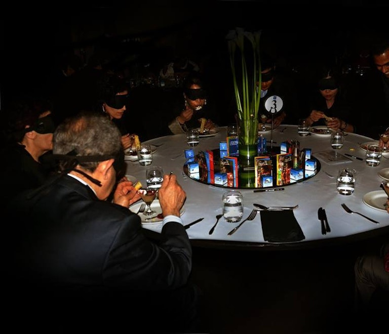 People having dinner in the dark for charity