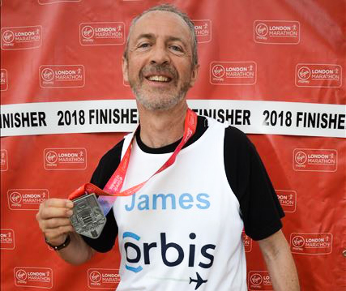 James, the London marathoner, brandishes his finishing medal