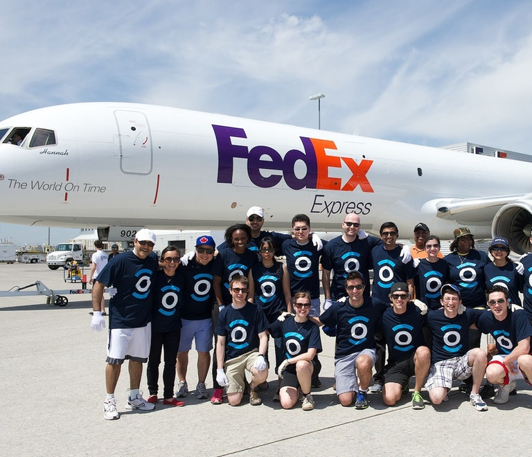 A group of people wearing Orbis T-shirts in front of a FedEx plane