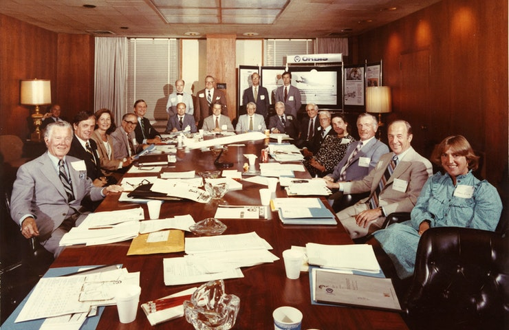 An old photo showing many original founding members of Orbis, sitting in a boardroom round a table
