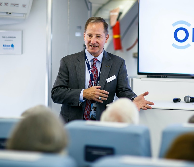 Orbis CEO Bob Ranck, wearing a suit, lectures on board the Flying Eye Hospital, a presentation on the screen behind him