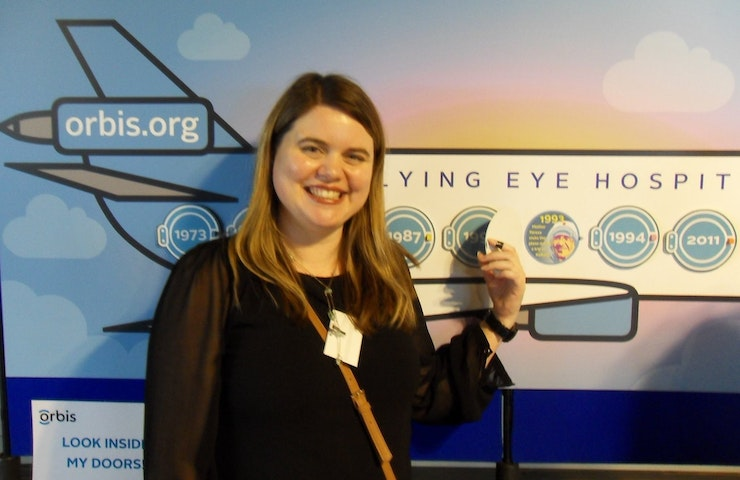 Volunteer Polly Holt stands in front of a Flying Eye Hospital timeline
