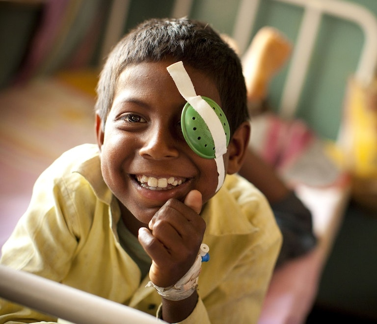 Young boy in a yellow shirt smiles at the camera, a big green eye patch taped on over his left eye