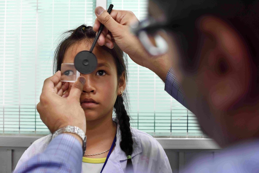 A young girl is examined for strabismus during a screening day during a Flying Eye Hospital Project in Vietnam