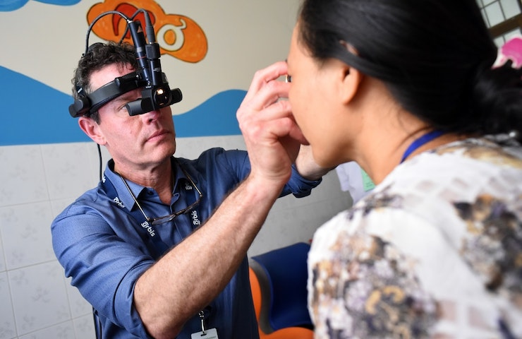 Volunteer eye surgeon gives eye exam.