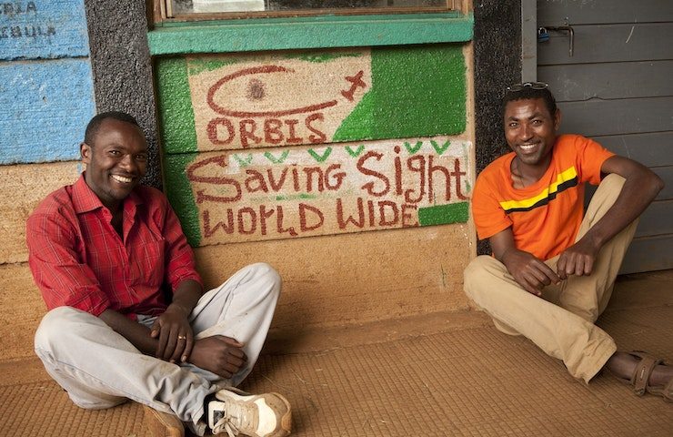 Men in front of Orbis saving sight worldwide logo.