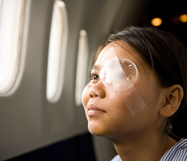 young Orbis patient looking out of Flying Eye Hospital window