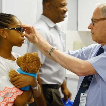 Orbis volunteer Dr. Rudy Wagner examines Savynna post strabismus surgery