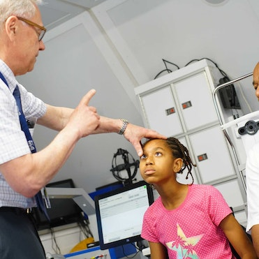 Orbis Volunteer Faculty Dr. Rudy Wagner examines Savynna before her strabismus surgery