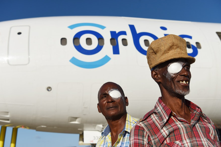 Two Barbadian men stand by the Flying Eye Hospital, wearing eye patches