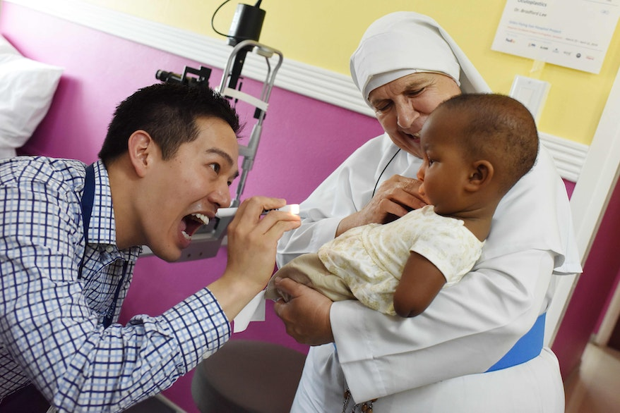 Orbis Flying Eye Hospital first time volunteer faculty Dr. Bradford Lee with a little patient in Jamaica