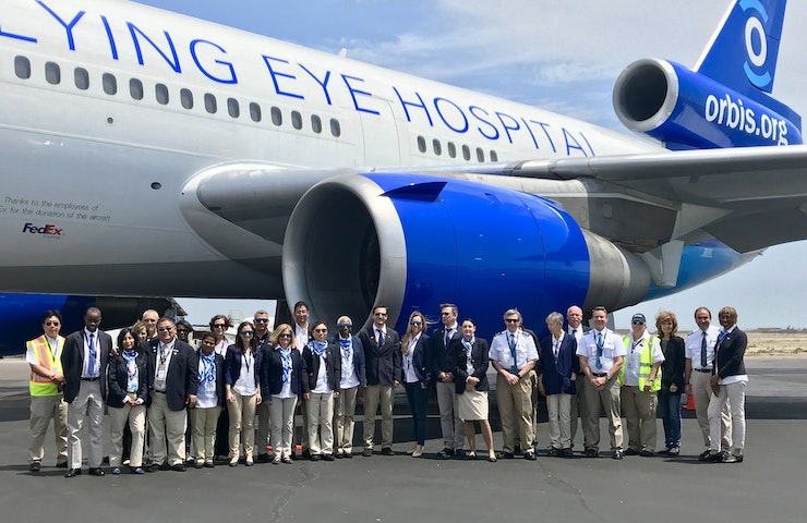 The Flying Eye Hospital crew stand in front of the plane after landing in Peru