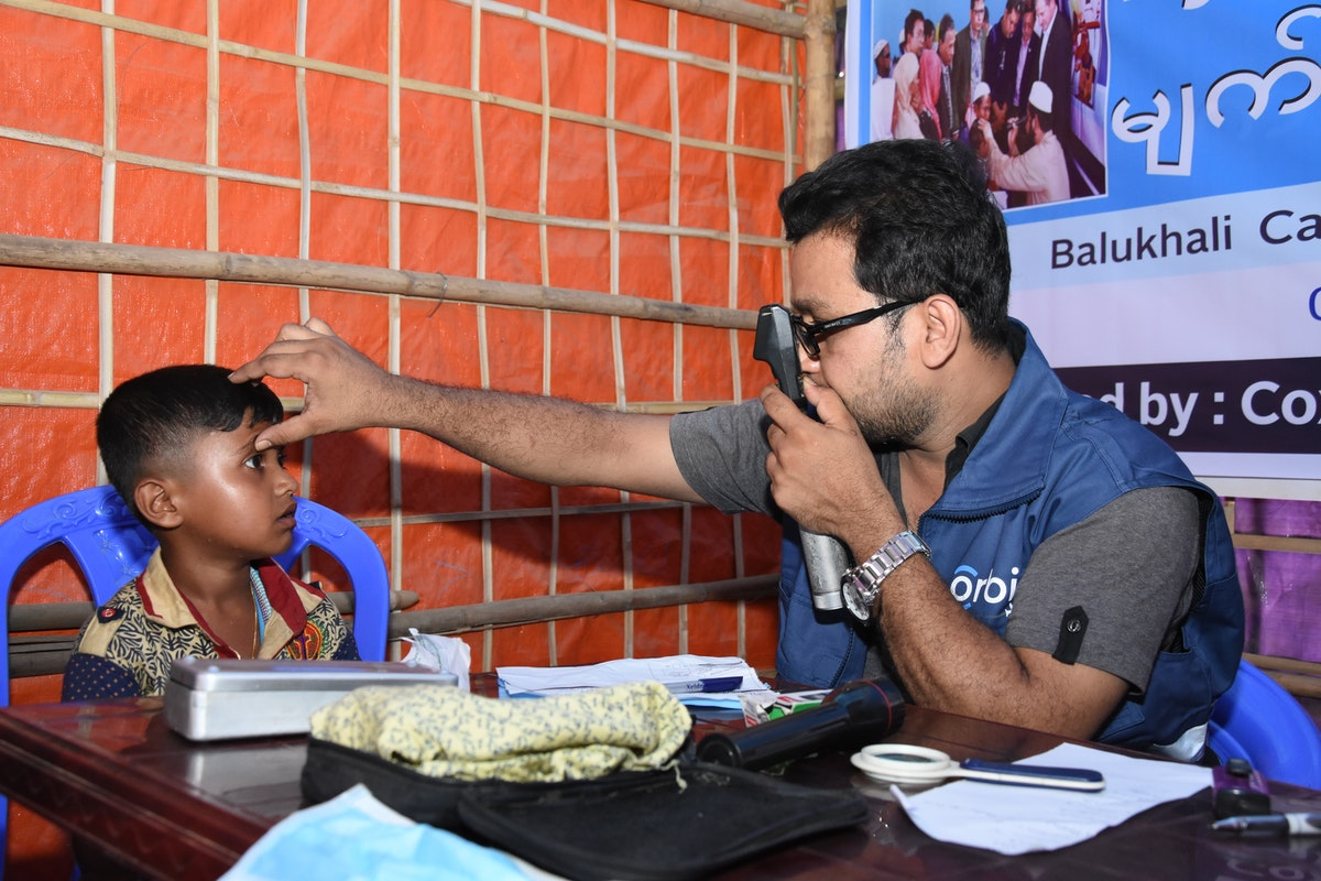 A young Rohingya boy has his eyes screened by an Orbis eye care worker