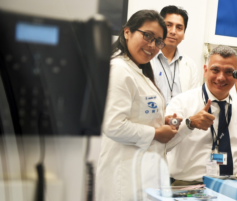 Trainees giving thumbs up as they work on an eye training dummy in Peru