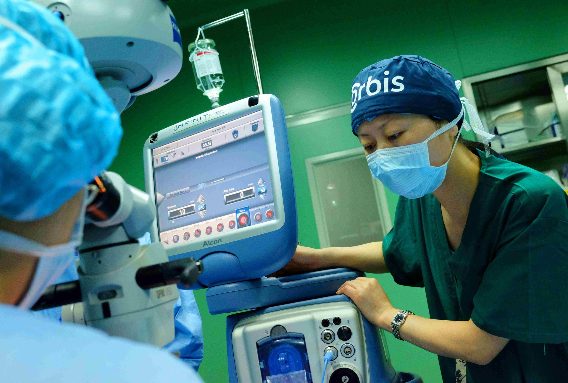 Xiao Ying, staff nurse in the operating room at Shandong Red Cross Eye Hospital adjusts irrigation levels on the Alcon Infiniti machine during a cataract extraction procedure.