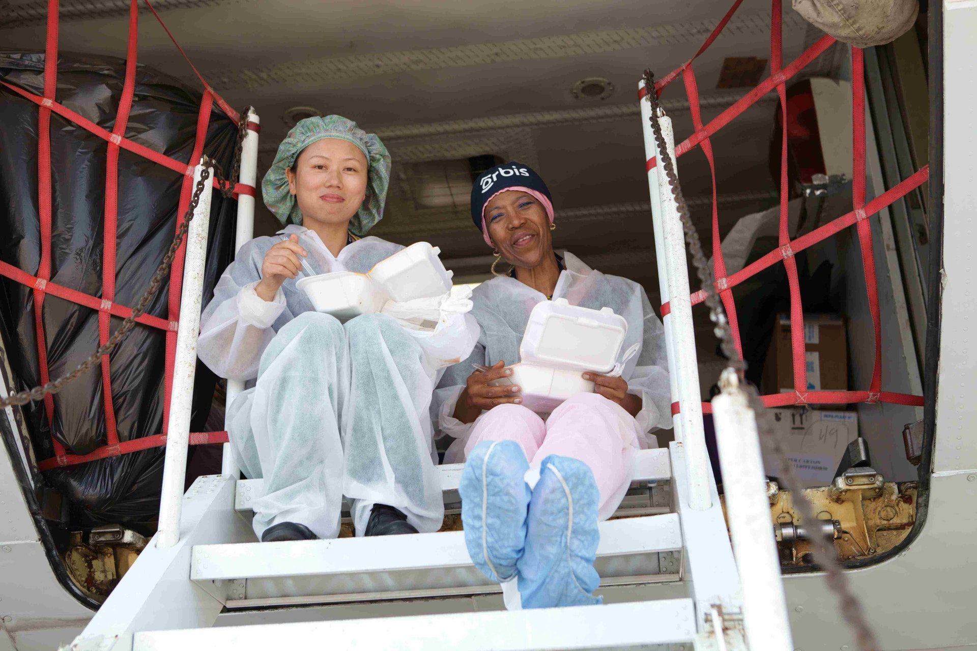 Angela Purcell, FEH head nurse and Xiao Ying Liu, FEH staff nurse enjoy their lunch break in the belly of the Flying Eye Hospital in Trujillo in 2015