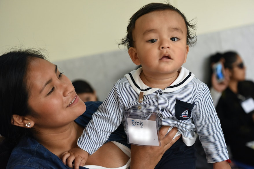 A Peruvian mother holds a baby up, dressed in a sailor top