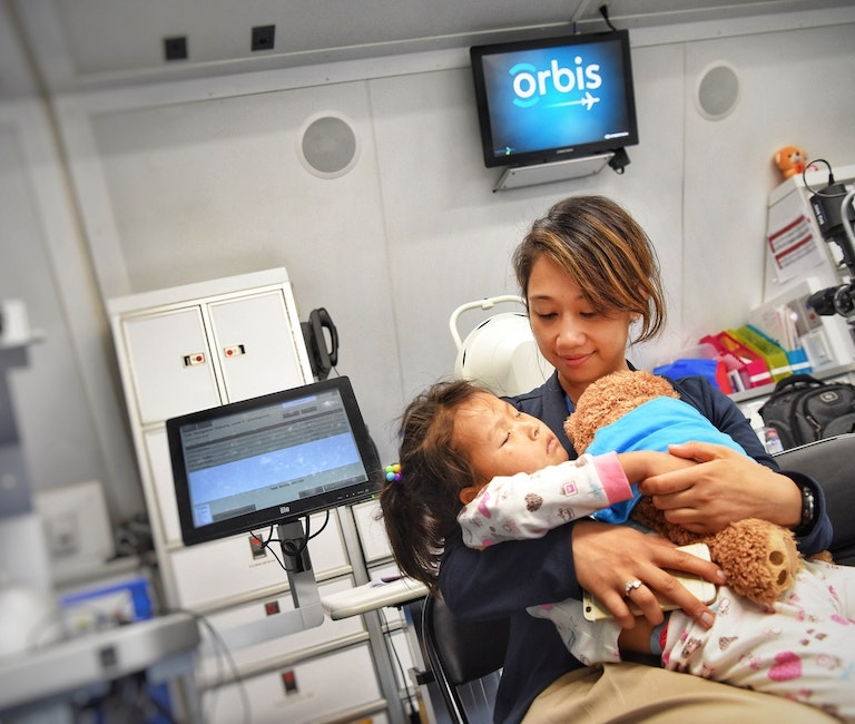 Orbis volunteer with patient on board the Flying Eye Hospital