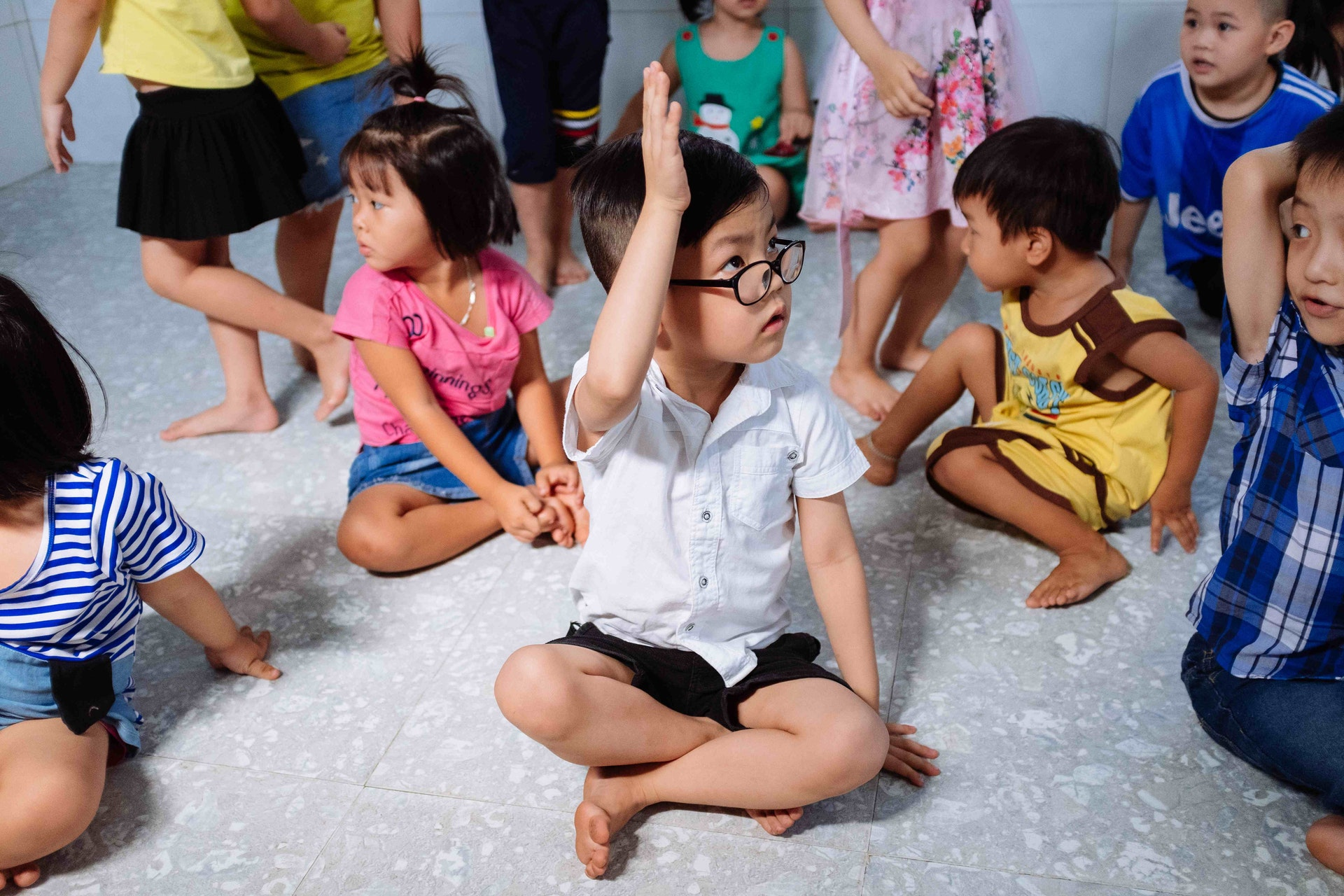 Cataract patient Tam, 5 years, sits with his school friends. He can see again after pediatric eye surgery